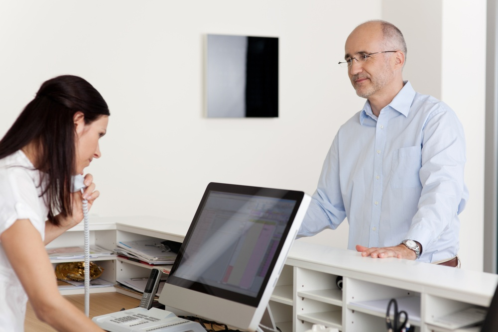 Mature male patient looking at female receptionist using landline phone and computer at reception .jpeg