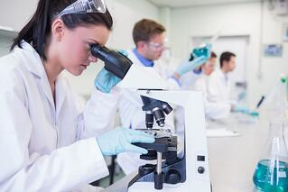 Side view of busy group of researchers working on experiments in the laboratory.jpeg