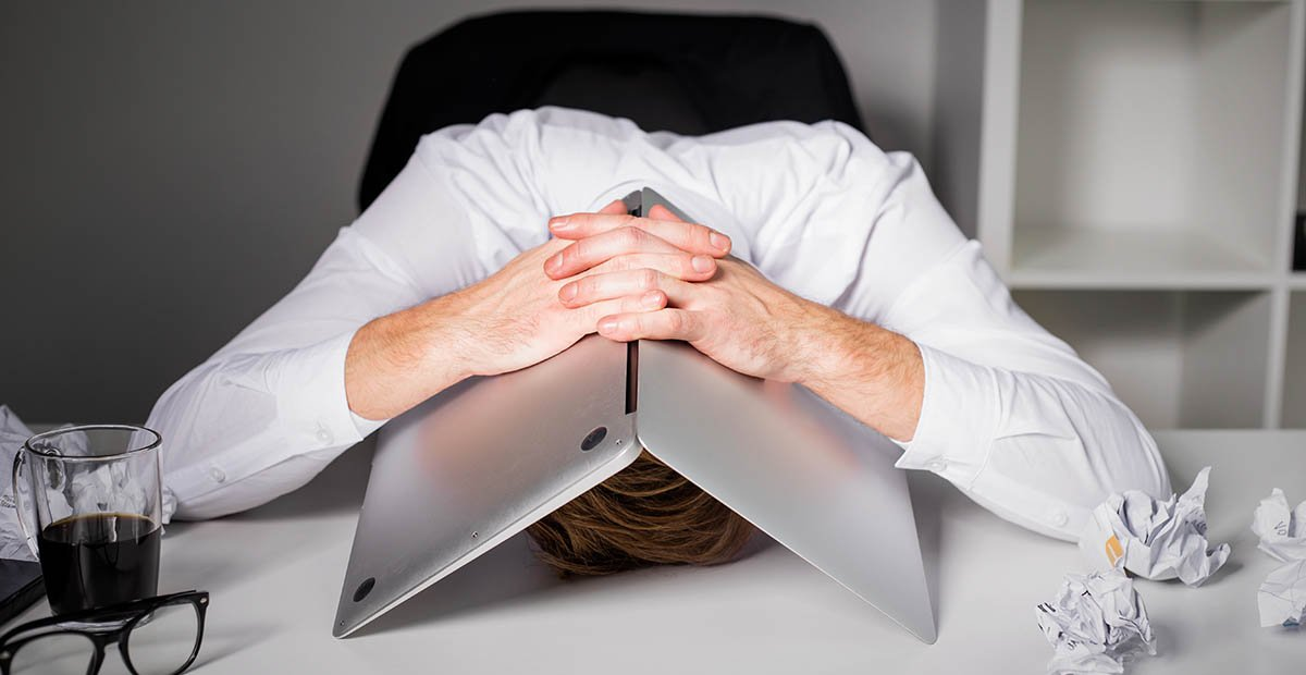 Frustrated man with laptop over head